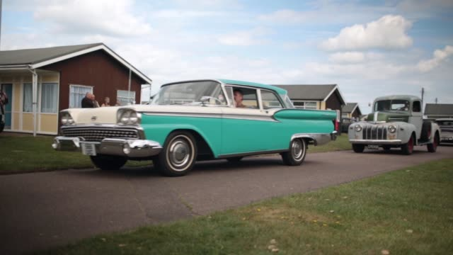 mid shot of classic american cars passing by fans of rock and roll rockabilly rockin' blues and americana gather at seacroft holiday camp in hemsby... - cultura americana video stock e b–roll
