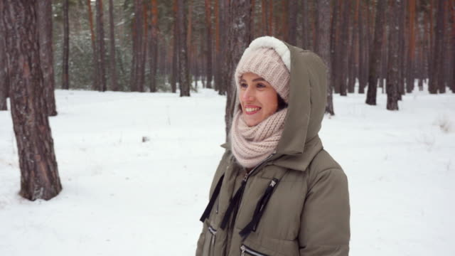 mid shot of exhilarated woman wearing winter clothes admiring a snowy panorama of woods - mitten stock videos and b-roll footage