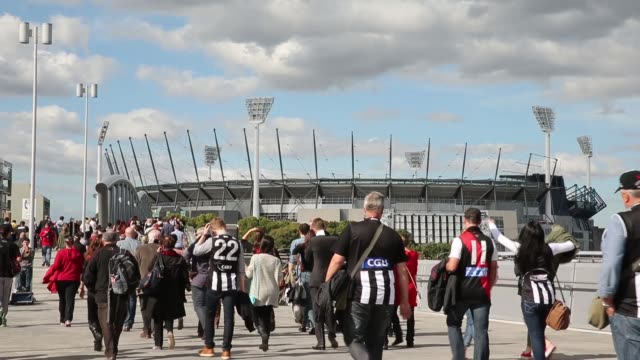 mid shot of football fans arriving to attend the afl anzac day match between the essendon bombers and the collingwood magpies at the melbourne... - parade stock videos & royalty-free footage