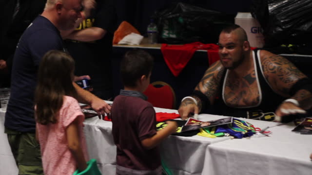 vídeos de stock e filmes b-roll de mid shot of former world wrestling entertainment wrestler brodus clay at an autograph signing during a wrestling event - autografar