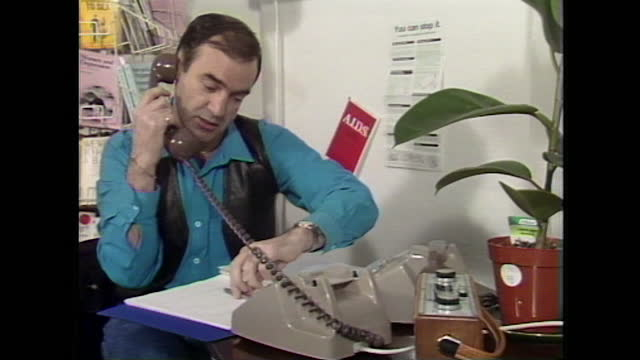 mid shot of man answering the phone at a desk of the sussex aids helpline office, uk; 1986. - customer service representative stock videos & royalty-free footage