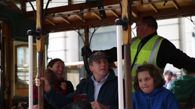 Mid shot of people aboard the cable car as it departs Tourists come from all over the world to see San Franciscos iconic cable cars the last manually...