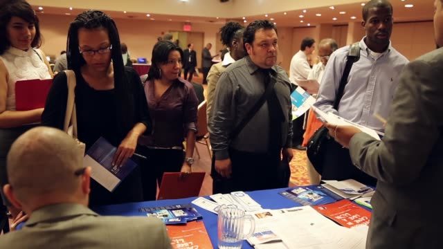 vídeos de stock e filmes b-roll de mid shot of people queueing to discuss various job opportunities job seekers meet potential employers at a job fair held in a conference room of the... - desemprego
