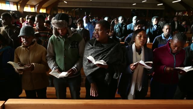 mid shot of people singing at church the congregation prays during a sunday service at regina mundi church in soweto on june 16 2013 in johannesburg... - afrikaans stock videos & royalty-free footage