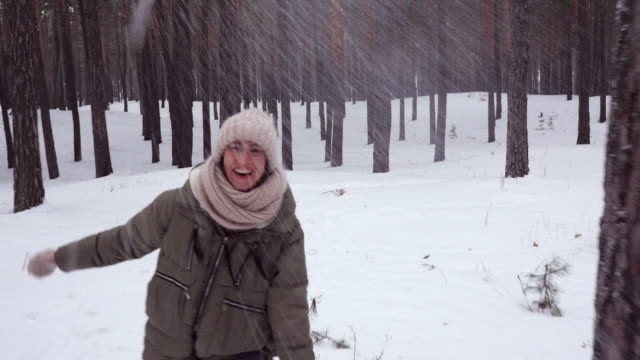 mid shot of positive woman throwing up snow in the snowy woods, playing with snow - mitten stock videos and b-roll footage