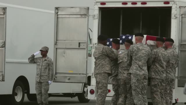 mid shot of soldiers putting a coffin into the back of a van bodies of seven servicemen killed in afghanistan return to us on may 07 2013 in dover... - 棺点の映像素材/bロール