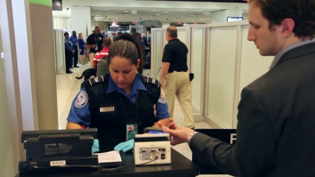 mid shot of tsa agent checking passengers documents at miami international airport. the program already in place at three other airports in the... - 金属探知機点の映像素材/bロール
