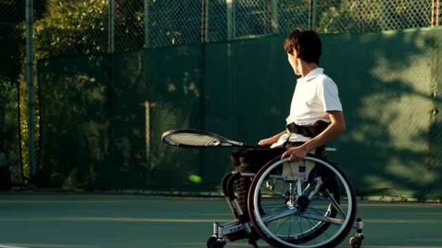 ダブルスをプレーする2人のアダプティブテニス選手のslo moミッドショット - テニス点の映像素材/bロール