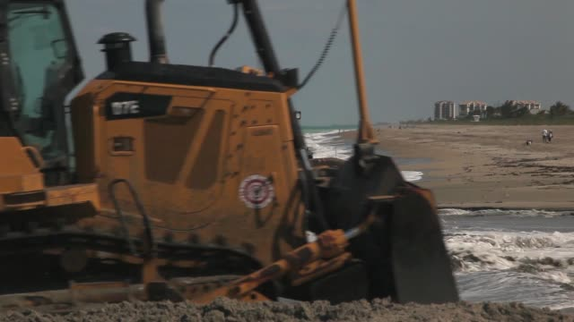 Mid shot of two bulldozers A bulldozer is used to push sand from a discharge pipe into place during a federally funded shore protection project by...