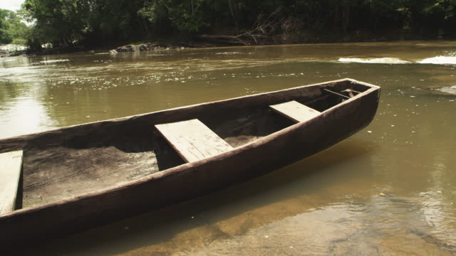 Mid shot of wooden canoe in the river