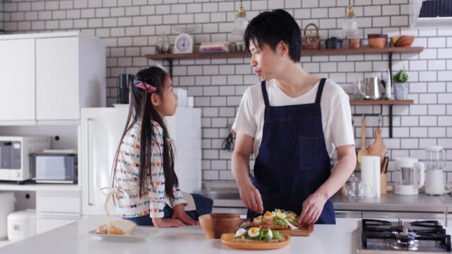 父が料理をしている間に娘と話している若い父親のミッドショット - daughter点の映像素材/bロール