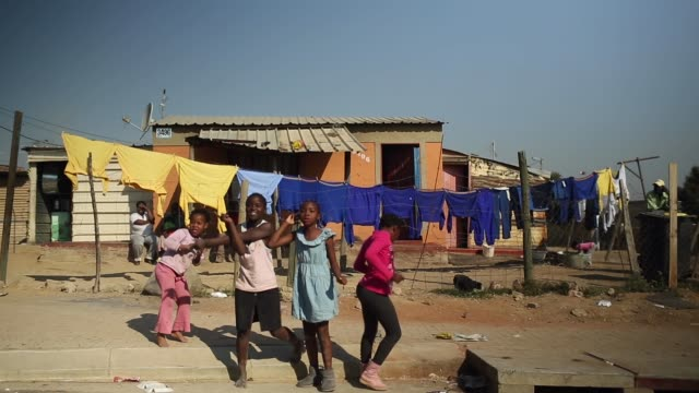 mid shot of young girls dancing residents of diepsloot township go about their daily activities as they pass the public holiday following youth day... - soweto stock videos & royalty-free footage