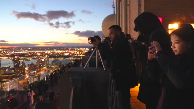 vídeos de stock, filmes e b-roll de mid shot, people photograph the view from the top of the rock observation deck in midtown manhattan, the empire state building , and the one world... - chicago 'l'