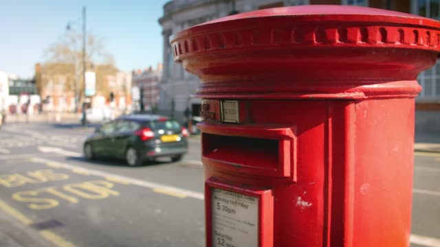 mid shot red post box with traffic in background - letterbox stock videos & royalty-free footage