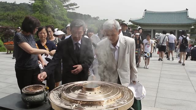 stockvideo's en b-roll-footage met mid shot south koreans burn incense during a ceremony marking korean memorial day at the seoul national cemetery on june 6 2013 in seoul south korea... - koreaanse etniciteit