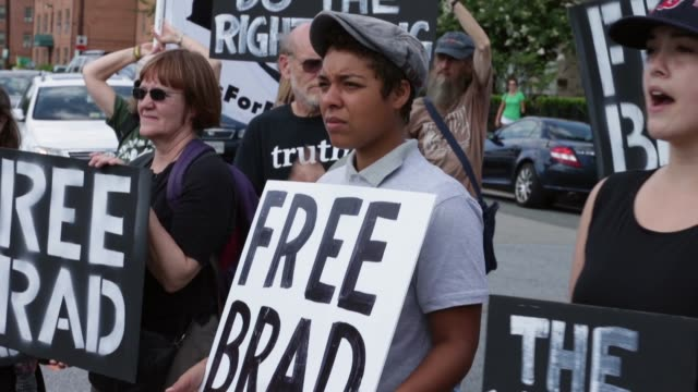 vídeos y material grabado en eventos de stock de mid shot supporters of us army private first class bradley manning protest his detention by marching around the perimeter and blocking the gates of... - petición