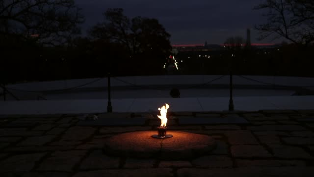 Mid Shot the eternal flame burns at the gravesite of the 35th President of the United States John F Kennedy at Arlington National Cemetery in...