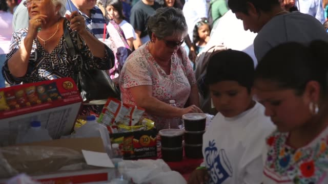 "Mid Shot thousands of people buy Mexican mole sauce dishes while attending the ""Feria de los Moles"" at la Placita park in downtown Los Angeles"