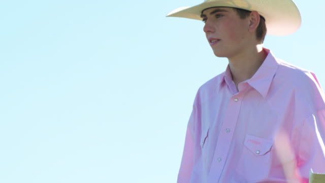 mid shot tilt portrait of a young cowboy standing in field holding lasso - cowboy hat stock videos & royalty-free footage