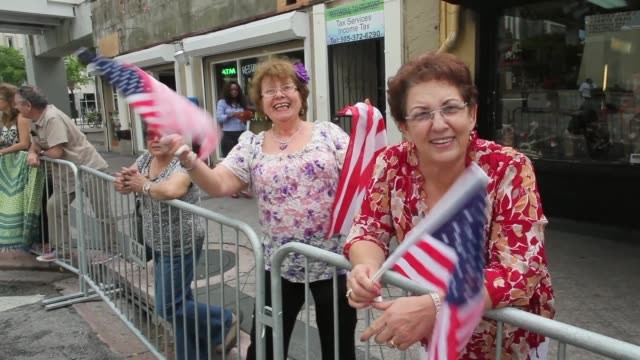 mid shot two spectating ladies wave a usa flag to honor veterans of the vietnam war the bay of pigs and all wars the city of miami holds the... - miami dade county bildbanksvideor och videomaterial från bakom kulisserna