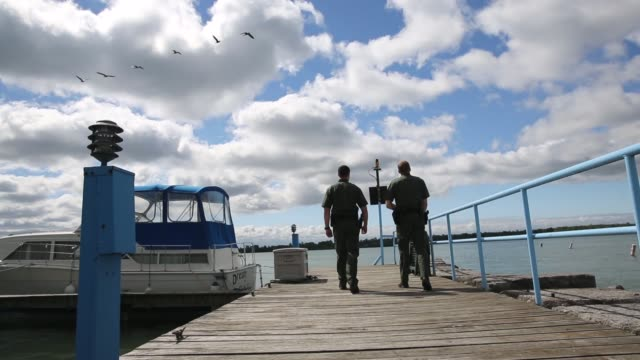 vídeos y material grabado en eventos de stock de mid shot us border patrol officers patrol along the niagara river which forms the uscanada border water laping the shore on the american side border... - río niágara