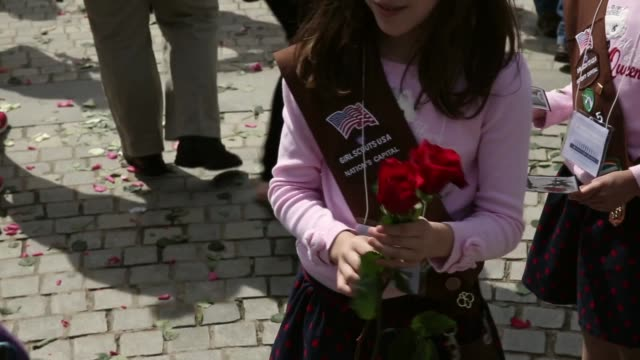 mid shot volunteers with memorial day flowers including cub scouts and girl scouts from local troops help to hand out roses at the entrance to... - cub scouts stock videos and b-roll footage