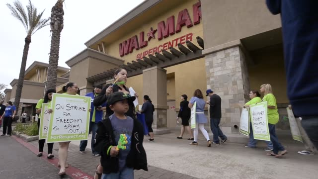 stockvideo's en b-roll-footage met mid shot walmart employees and their supporters walk a picket line to protest walmart's retaliation against workers who speak out on may 30 2013 in... - wal mart