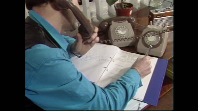 mid shots of a man talking on the phone and writing down notes at the sussex aids helpline office, uk; 1986. - customer service representative stock videos & royalty-free footage