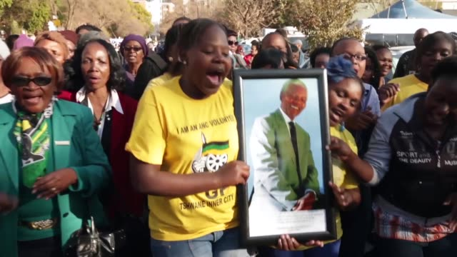 mid tracking shot of women holding a picture of nelson mandela as they dance and sing out his name. well-wishers and members of the african national... - ハウテング州点の映像素材/bロール