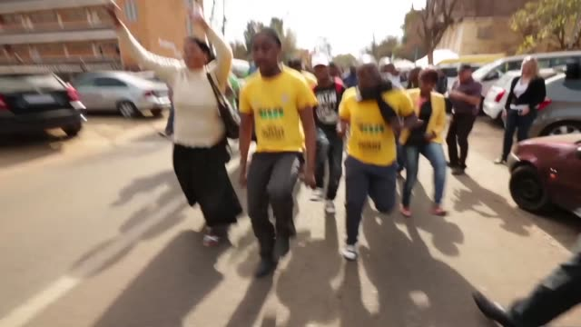 Mid tracking shot wellwishers and members of the African National Congress Youth League rally with song and dance outside the Mediclinic Heart...