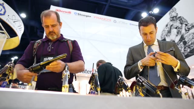 mid two shot of men trying out revolvers during the 2013 nra annual meeting and exhibits at the george r brown convention center on may 4 2013 in... - national rifle association stock videos & royalty-free footage