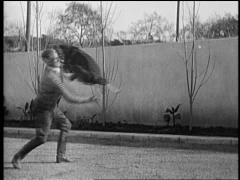 B/W mid1920s Rin Tin Tin jumping into arms of trainer Lee Duncan / newsreel