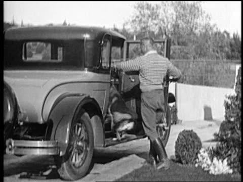 stockvideo's en b-roll-footage met mid-1920s trainer lee duncan putting rin tin tin in car + climbs in after him / newsreel - alleen één mid volwassen man