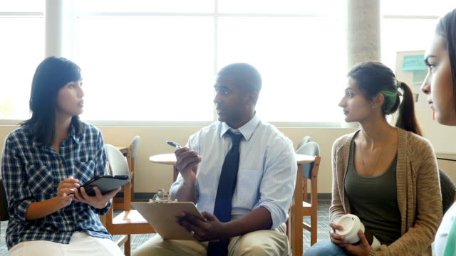 Mid-adult African American male teacher leads discussion group in library at STEM high school