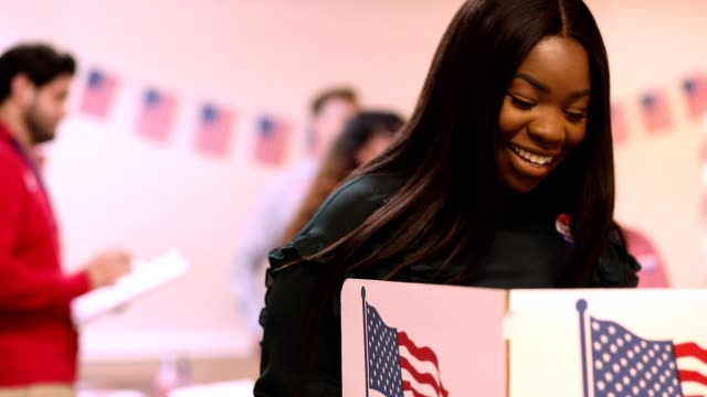 mid-adult, african descent woman votes in usa election. - voting stock videos & royalty-free footage