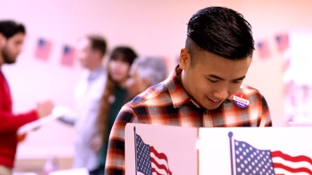 mid-adult, asian descent man votes in usa election. - local politics stock videos & royalty-free footage