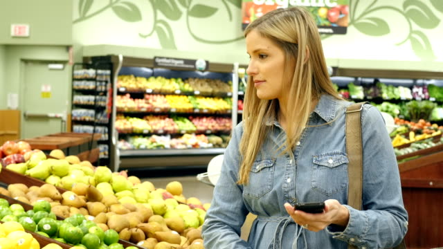 Mid-adult Caucasian female customer in produce department in local supermarket checks grocery list on her smart phone