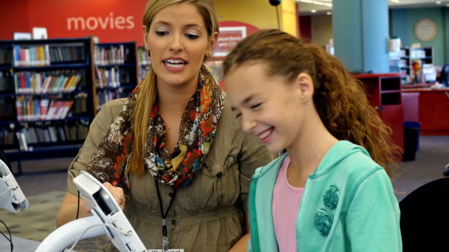 mid-adult caucasian female librarian demonstrates how to use a tablet or book check out equipment in library - hair back stock videos & royalty-free footage