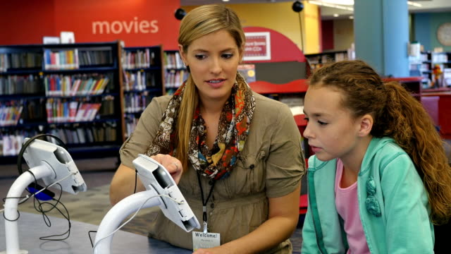 mid-adult caucasian female librarian teaches elementary age student how to use check out equipment in library - hair back stock videos & royalty-free footage