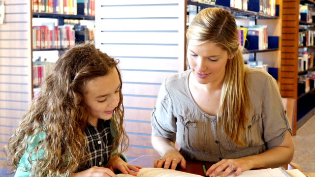 mid-adult caucasian home school mother helps daughter with reading assignment in library - hair back stock videos & royalty-free footage