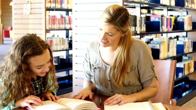 mid-adult caucasian home school mother or tutor helps elementary school girl with reading assignment - hair back stock videos & royalty-free footage