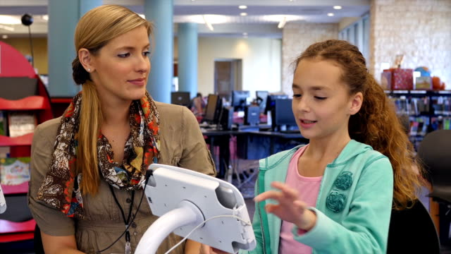 mid-adult caucasian librarian supervises an elementary age girl on using library tablet or book check out equipment - hair back stock videos & royalty-free footage