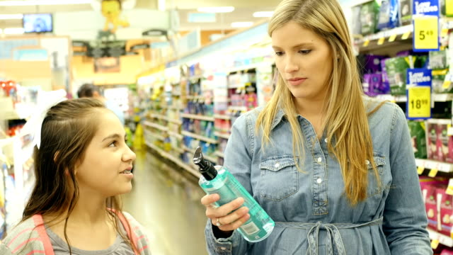 mid-adult caucasian mother and her hispanic elementary age daughter shop in personal care aisle of supermarket - shampoo stock videos & royalty-free footage