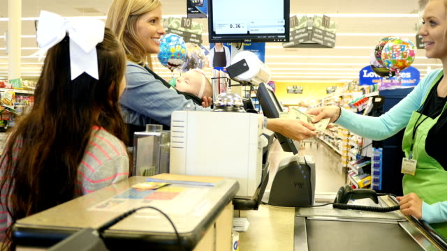 mid-adult caucasian mother hands cash to young caucasian female cashier to complete transaction at supermarket - checkout stock videos and b-roll footage