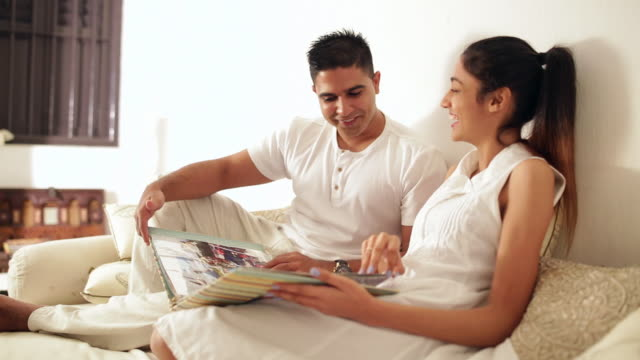 ws mid-adult couple looking at photo album on sofa / singapore - mid adult couple stock videos & royalty-free footage