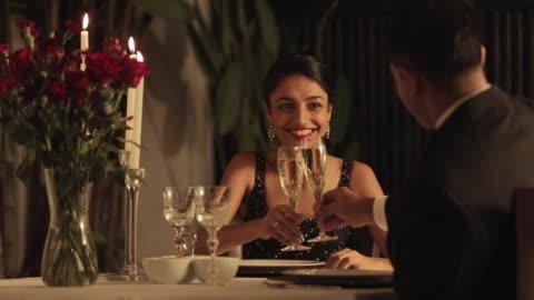 ms mid-adult couple raising toast at restaurant / singapore - mid adult couple stock videos & royalty-free footage