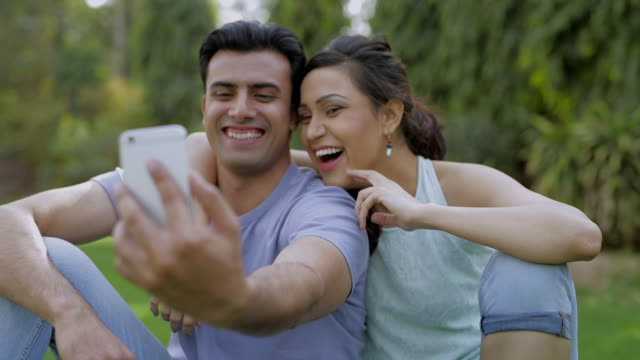ms selective focus mid-adult couple taking selfie in park / india - mid adult couple stock videos & royalty-free footage