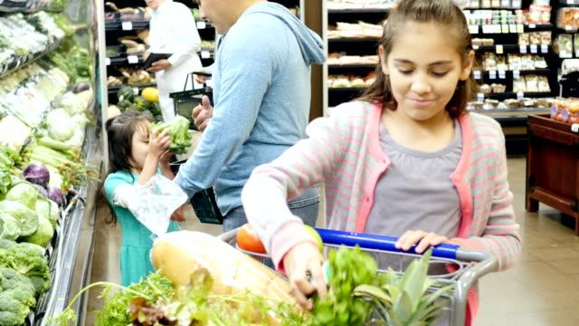 Père hispanique adulte Mid-boutiques pour produire avec son Âge élémentaire et Enfant d'âge pré-scolaire fille dans un supermarché