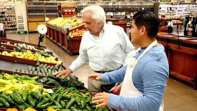 mid-adult hispanic male assists caucasian senior customer as he shops for peppers in local supermarket - assistant stock videos and b-roll footage