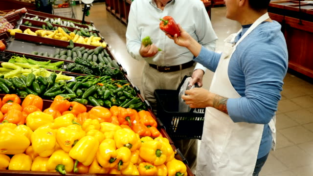 mid-adult hispanic male supermarket employee assists senior caucasian male customer as he selects peppers in local supermarket - mid adult men stock videos & royalty-free footage